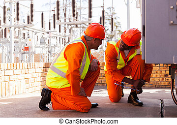 electricians discussing work in electrical substation - two...