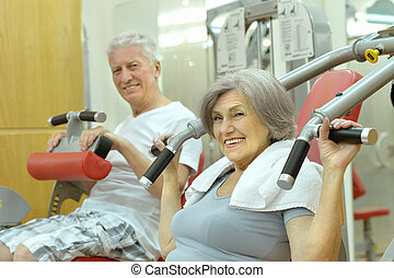 Senior Couple Exercising In gym - active smiling senior...