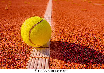 Yellow tennis ball touching the line on red clay court