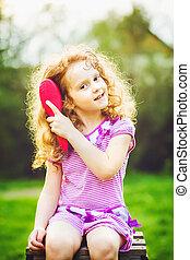 Smiling little curly girl brushing her hair