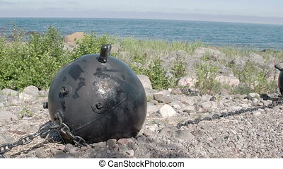 A big black sea mine on top of a hill near the sea