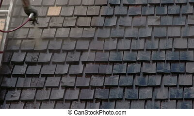 Cleaning of the newly installed wooden shingles from the...