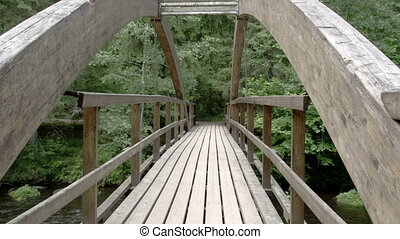 The wooden hanging bridge on the forest This bridge serves...