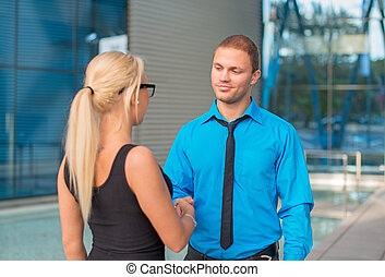 Business meeting. Man and woman shaking hands outdoors.