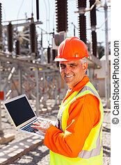 senior electrician using laptop - smiling senior electrician...