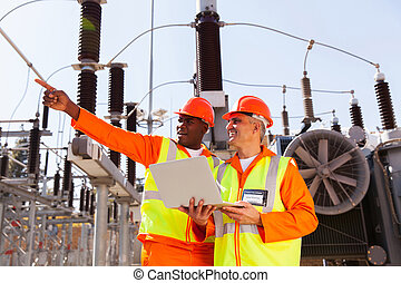 senior technician with co-worker working together in power...