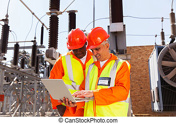 two electrical technicians using laptop - two modern...