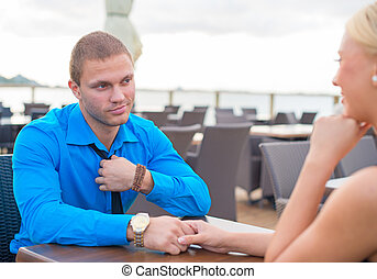 Man making proposal to woman in outdoor cafe.