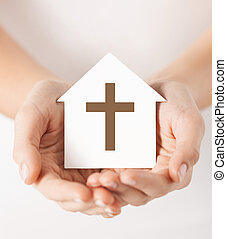 hands holding paper house with cross symbol - religion,...