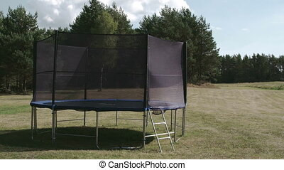 A small size trampoline on the backyard of the house. It is...