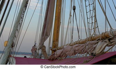 Ropes and rolled big clothes on the sail mast of the ship....