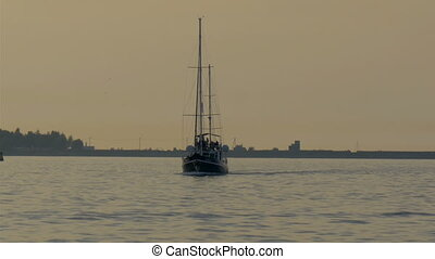 A small yacht on sail on the ocean water. There are...