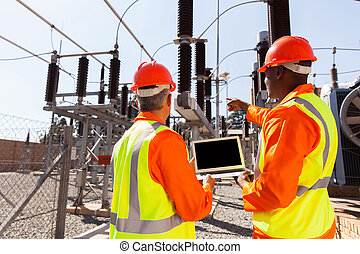 electricians with laptop pointing - rear view of...