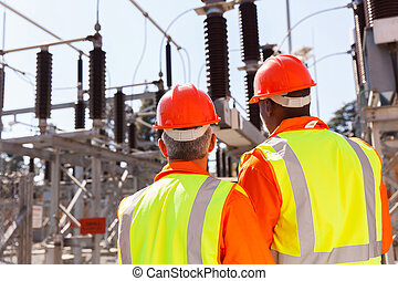 back view of two electrical engineers in substation