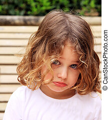 sulking - a young child with a pretty face sulking and...