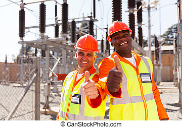 two technicians giving thumbs up - two cheerful technicians...