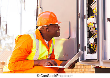 african electrician checking computerized machine status -...