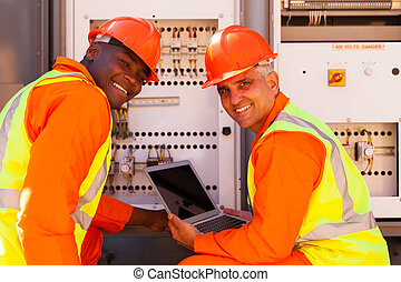electrical co-workers using laptop computer - modern...