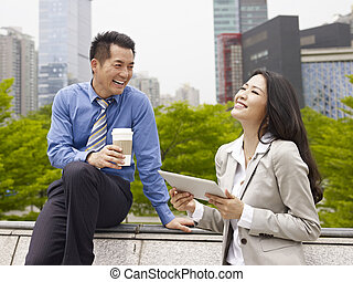 colleagues - asian businessman and businesswoman talking...