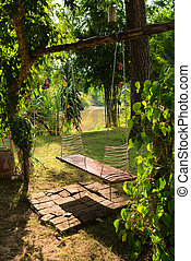 Lone swing seat in a tropical park - Sunny lone wooden swing...