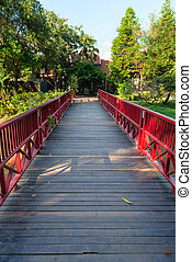 Wooden bridge with red fence  in green tropical park