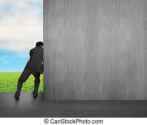 man push away concrete wall with sky and grass background