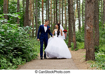 Bride and groom - The bride and groom walk down the path in...