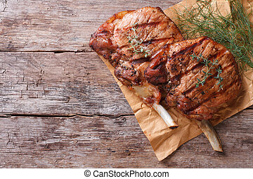 grilled pork with herbs on an old table top view close-up -...