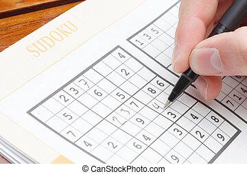 Solving sudoku - A person solving a sudoku puzzle
