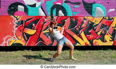 Street dancer - Young woman dancing in front of street wall...