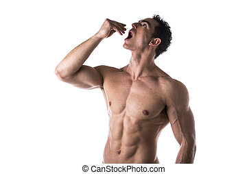 Strong muscular man taking diet supplements or...