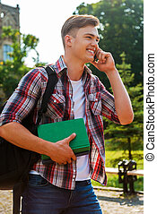 In touch with his friends Handsome male student talking on...