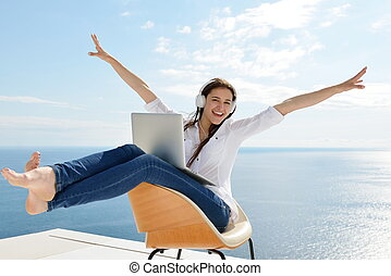 relaxed young woman at home working on laptop - beautiful...