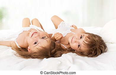 happy children girls twin sisters in bed