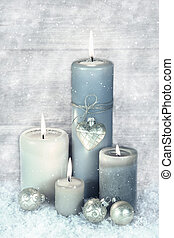 Four blue, grey and white burning christmas candles with...