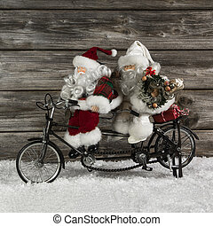 Two funny santa claus on a tandem in hurry for christmas...
