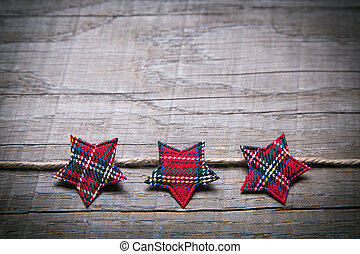 Wooden christmas background with three red checked stars as...