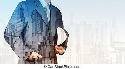 Double exposure of business engineer and abstract city as...