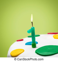 Burning candle with the number one on a birthday cake