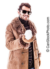 Holding a Snowball - a young man wearing a sheepskin coat...