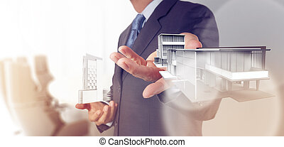 businessman hand presents house model on modern computer as...