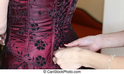 girlfriend tying corset red black dress with lace bride