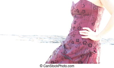 burgundy dress developing in the wind on a woman that stands...