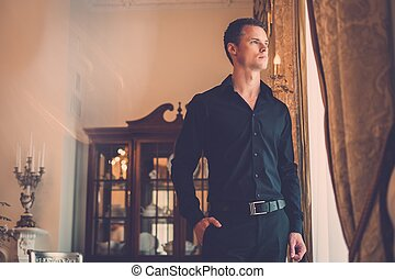Handsome young well-dressed man in luxury house interior