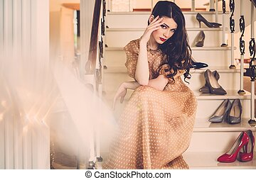 Beautiful young lady sitting on a steps in luxury house interior
