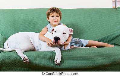 small happy girl on couch with dog