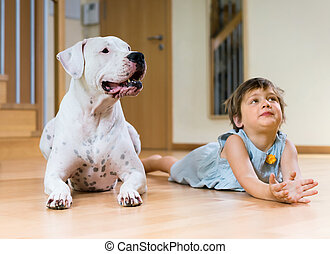 Cute female toddler on the floor with dogo Argentino (focus...