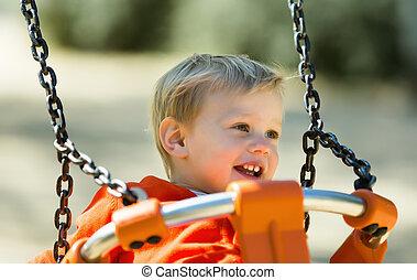 laughing toddler on orange swing