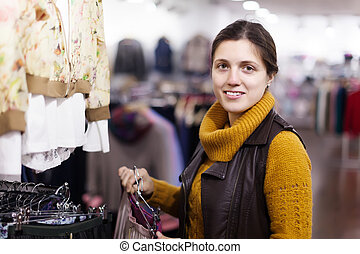 woman choosing skirt at clothing store