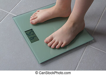 child weighing up - Child with bare feet on a bathroom scale...